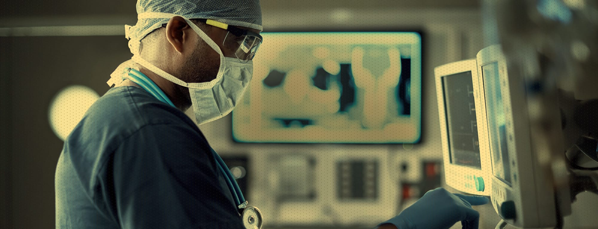 Medical doctor in operating room intently focuses on a computer screen