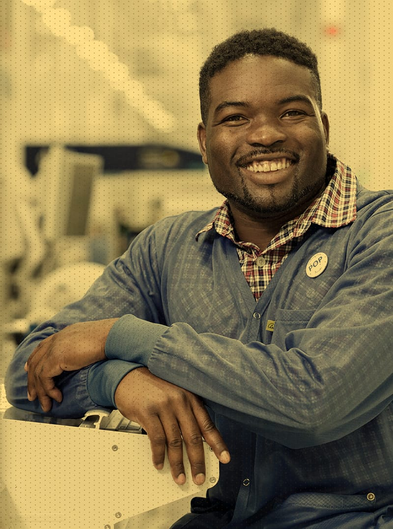 Man sitting by machine smiling at camera