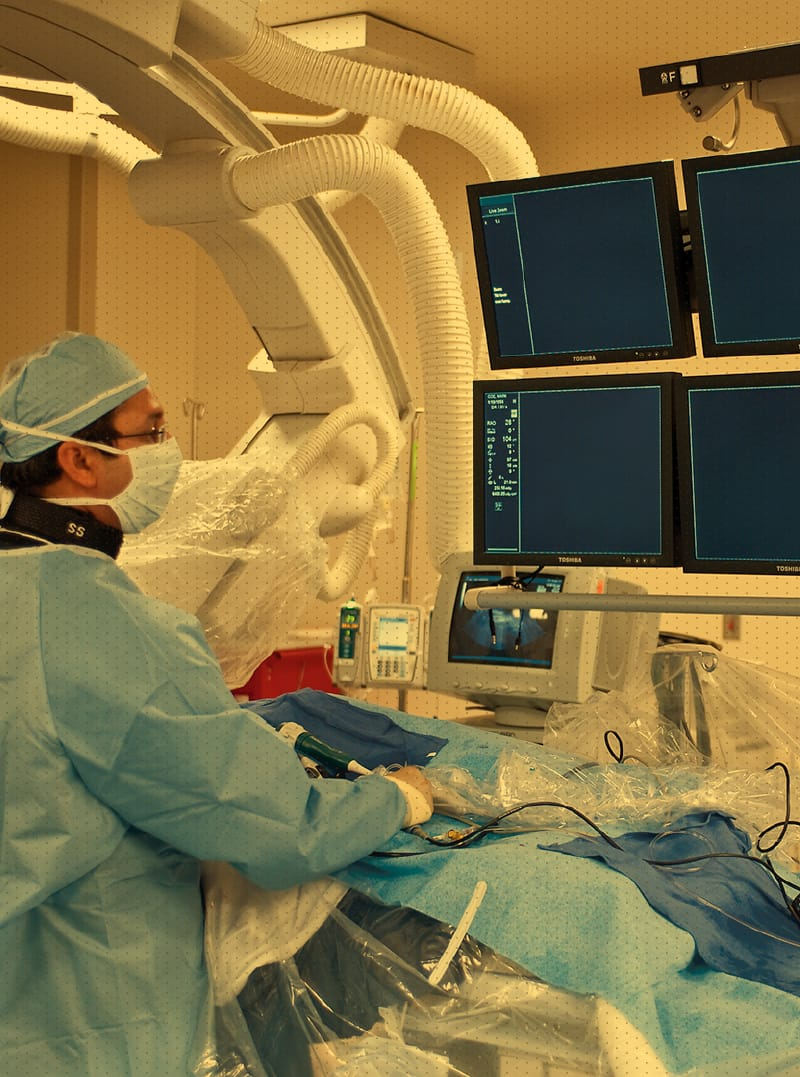 Surgeon in scrubs looking at screens during procedure
