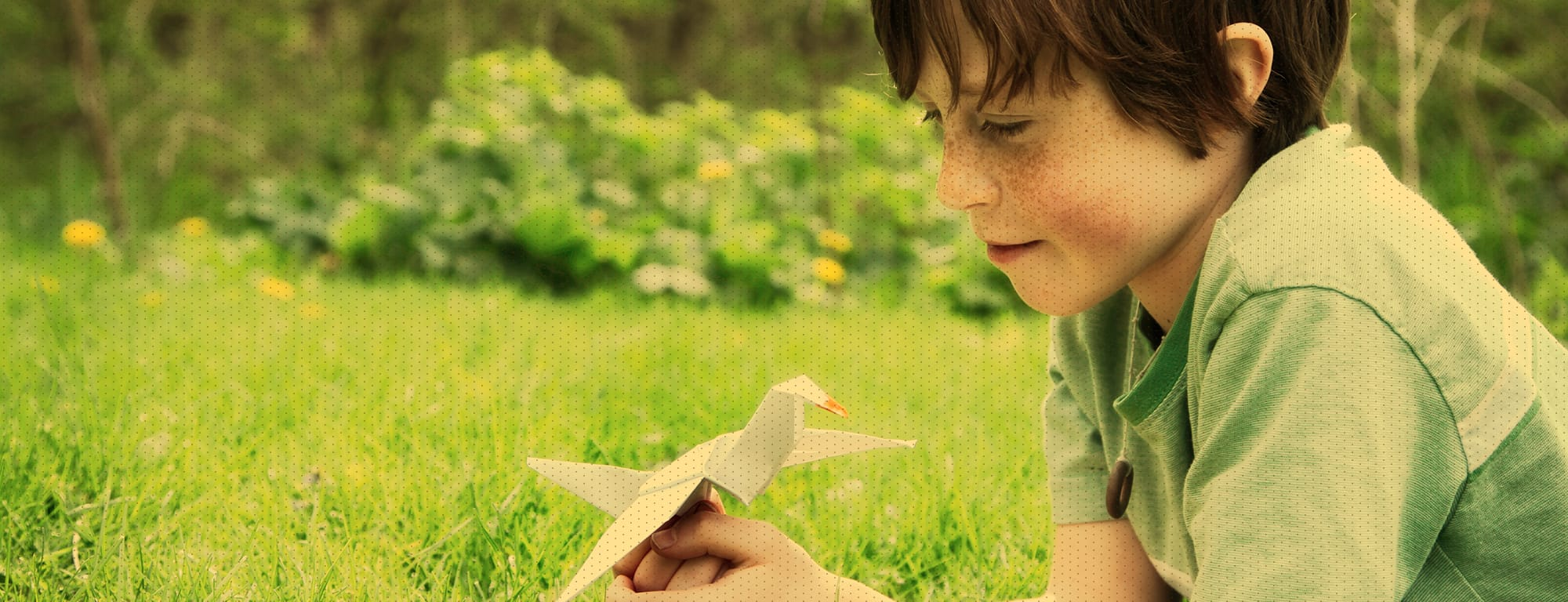 Little boy laying in grass, smiling and holding an origami bird made of paper